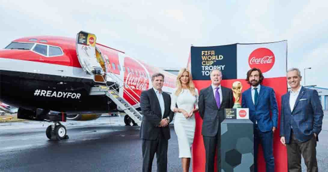People in business attire posing with World Cup trophy in front of Coca Cola airplane