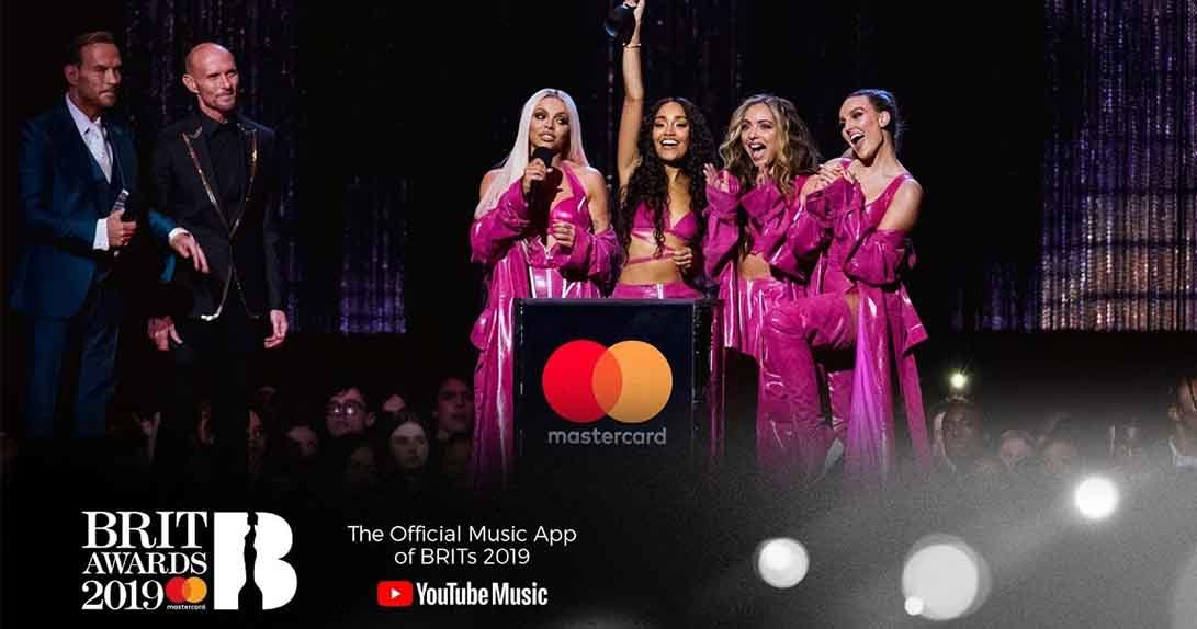 Little Mix group members holding award at podium