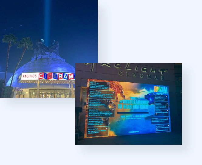 View of the Cinerama Dome in Hollywood with a Godzilla head on top of the dome with a blue light coming out of his mouth and a twitter wall visualizing tweets.