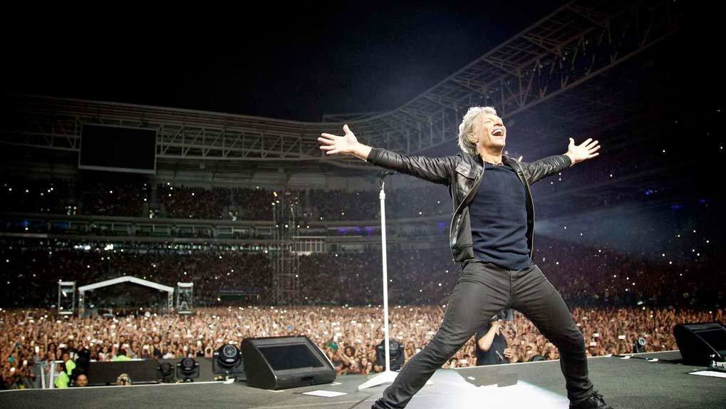 Bon Jovi performing in front of huge stadium crowd
