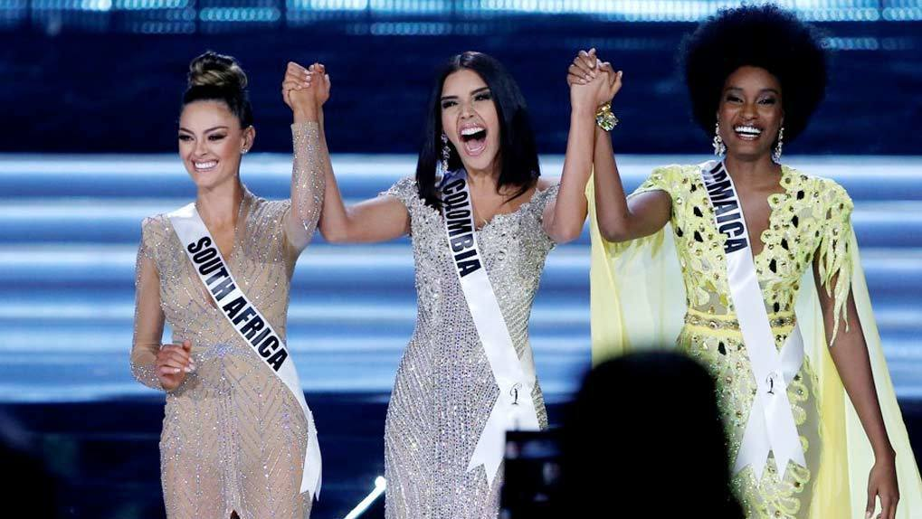 Image of three Miss Universe contestants on stage