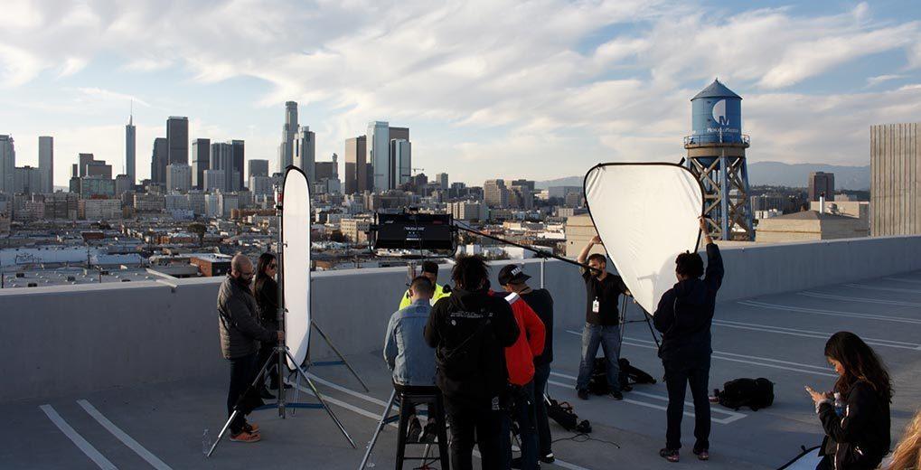 Film crew on rooftop surrounding the music artist Khalid