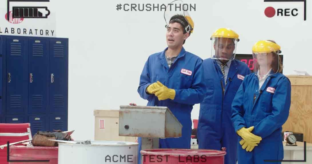 Three people in blue jumpsuits and hard hats
