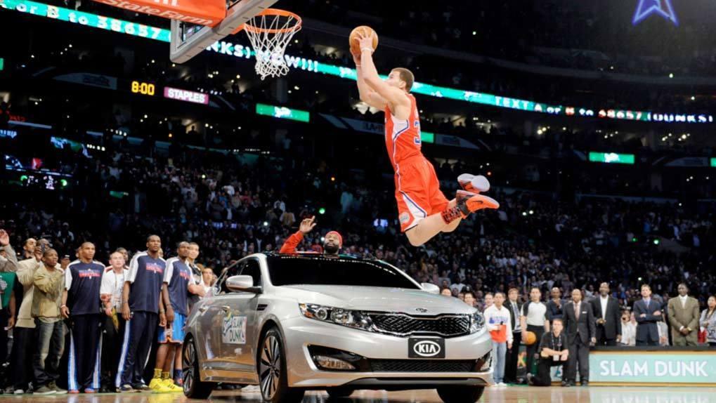 NBA player slam dunking over KIA on basketball court