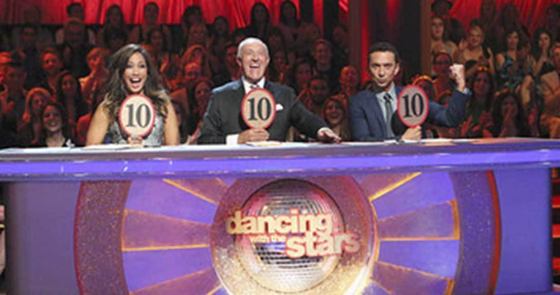 Dancing with the Stars Judges sitting at table holding up scoring paddles