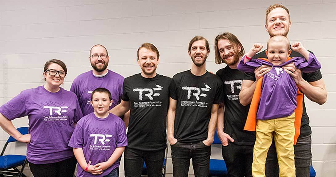 Imagine Dragons and a family with little boy wearing cape