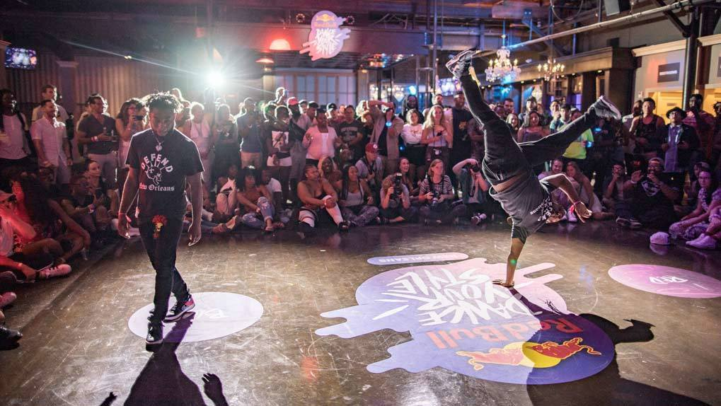 Two men dance batteling in front of audience where one man is doing a one arm handstand