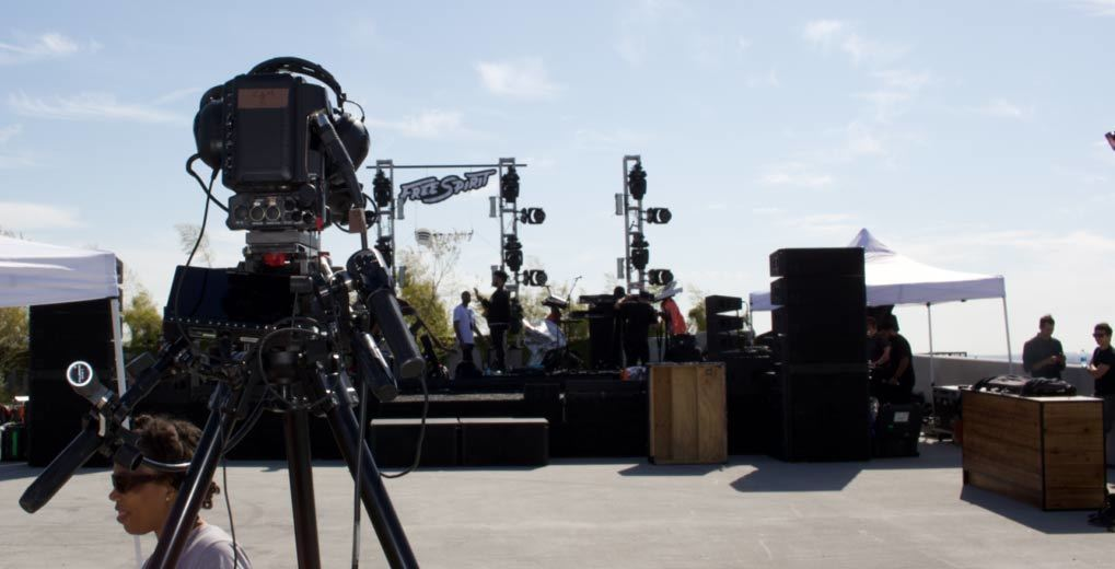 Film crew on rooftop with video equipment pointing towards a rooftop stage