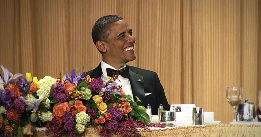 Barack Obama sitting at table smiling