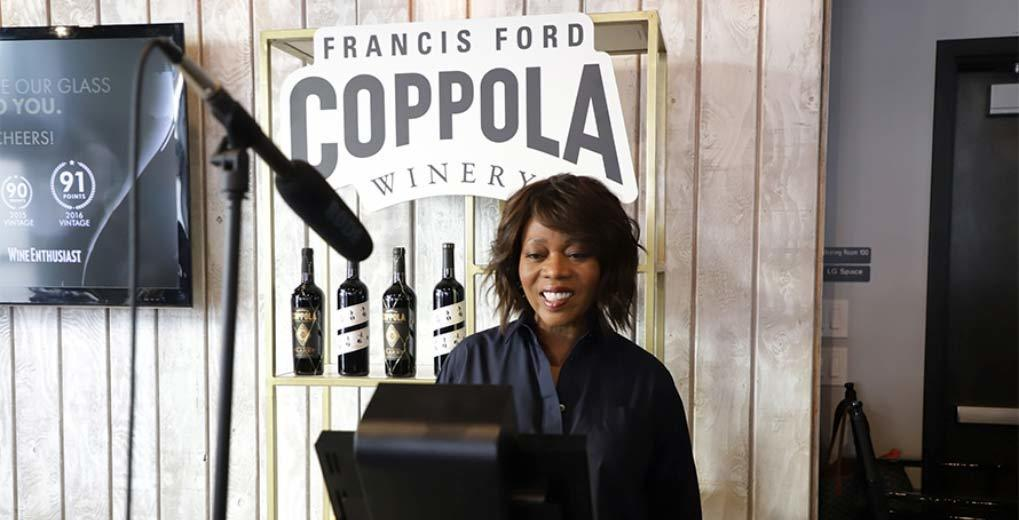 Image of Alfre Woodard recording a video on the custom kiosk with a microphone and Francis Ford Coppola Winery sign and wine bottles behind her.