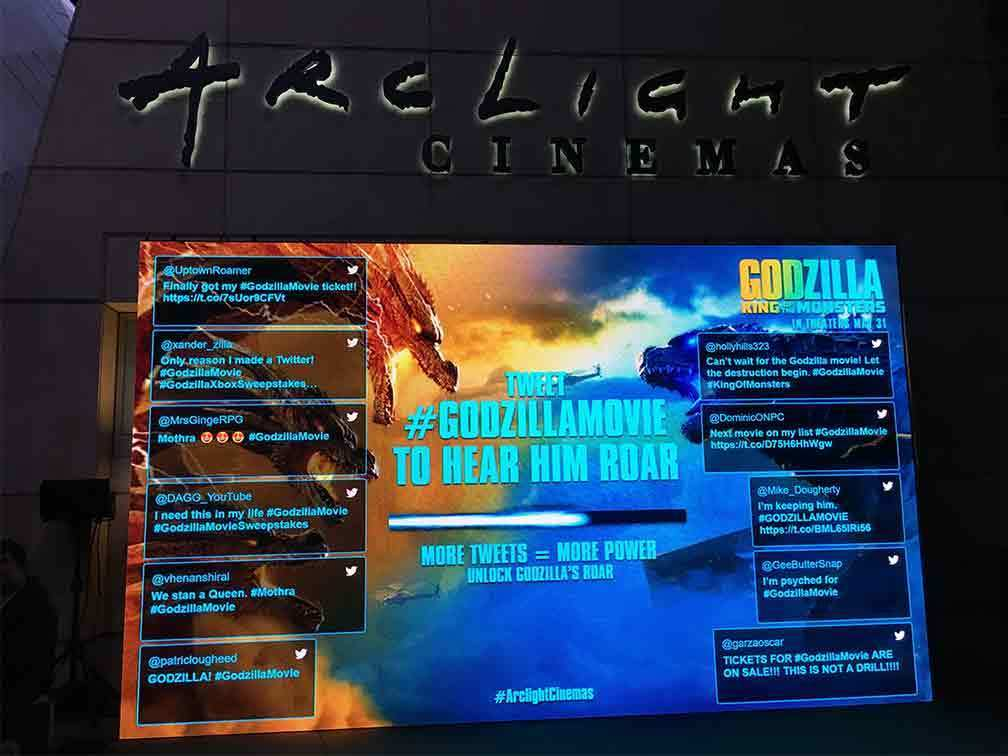 Godzilla jumbo screen displaying tweets from users