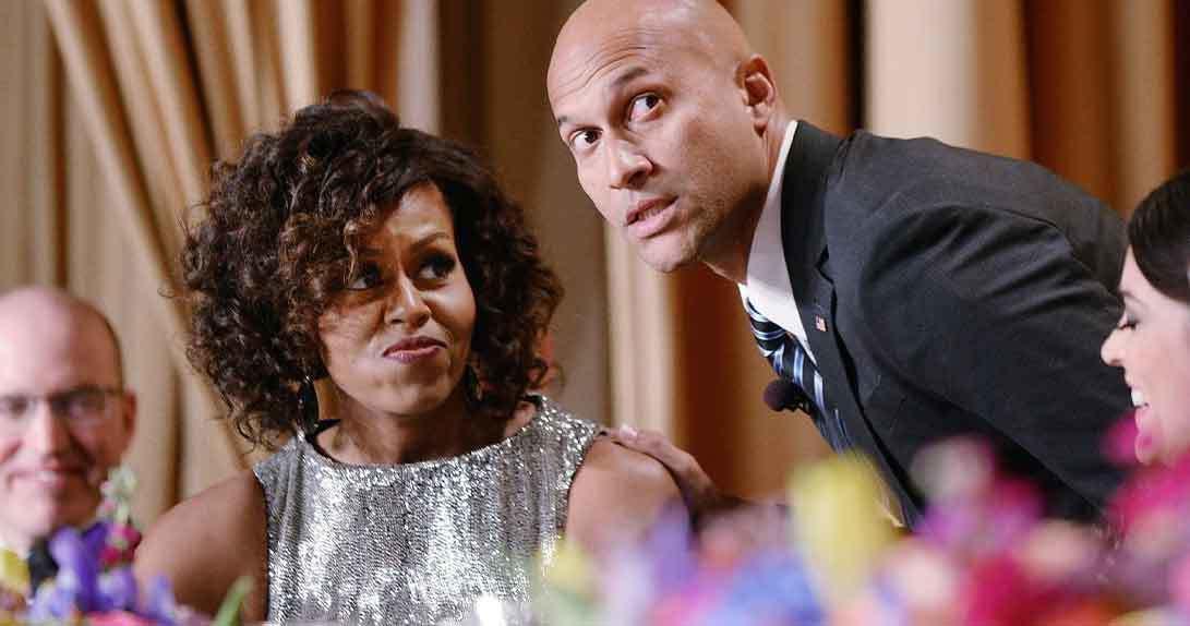 Michelle Obama sitting with Michael Keegen Key next to her
