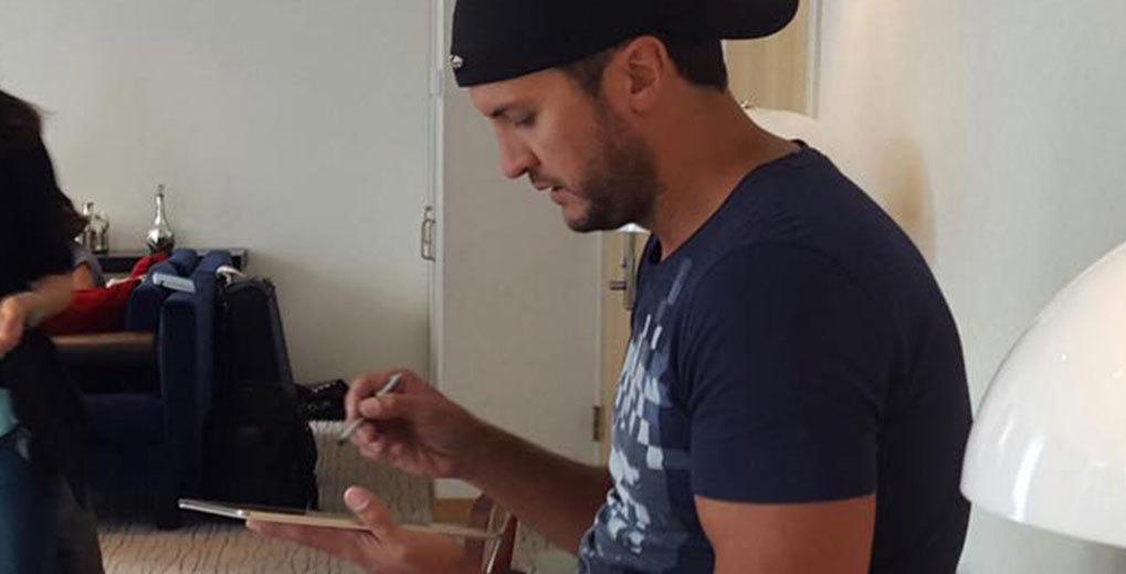 Luke Bryan holding tablet and stylus