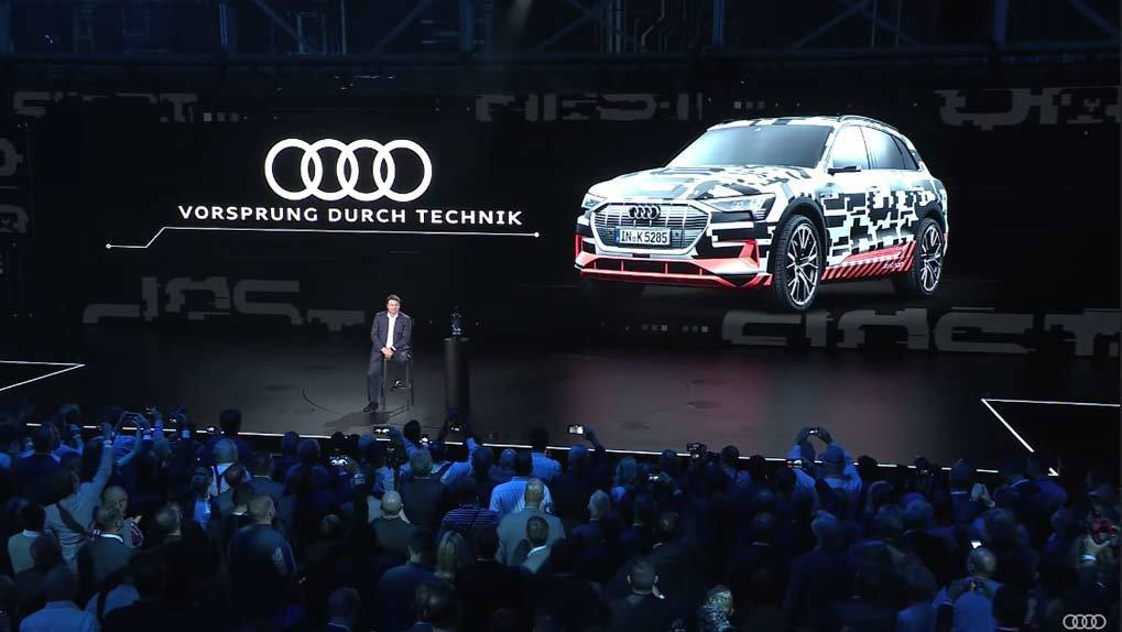 Man on stage with Audi car backdrop